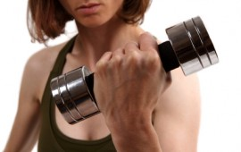 Lady strength training with dumbell.