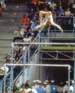 Olympic Medal winning Gymnast Olga Korbut perfoming a bar flip.